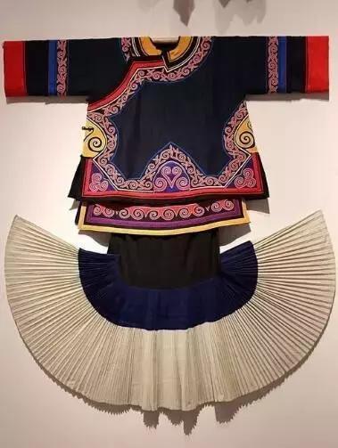 彝族男子穿黑色窄袖且镶有花边的右开襟上衣,下着多褶宽脚长裤.
