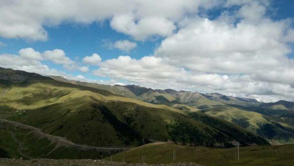 这一段路风景绝佳,从山路下来是广阔的草原,辽远的蓝天