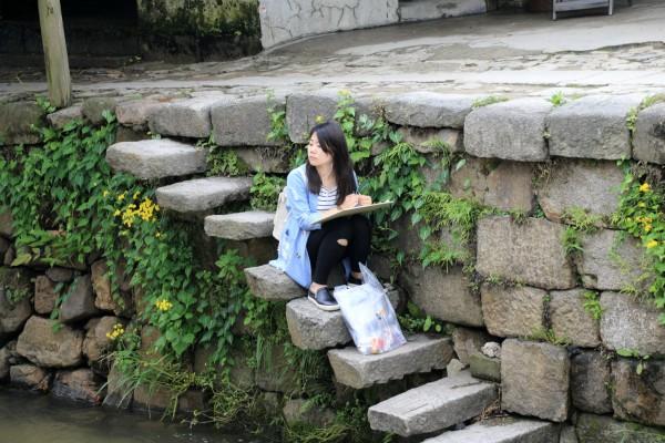 一个女孩子坐在等级上画着前面的石桥.石墩建筑设计体育图片